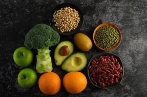 Brokkoli, Apfel, Orange, Kiwi, Avocado und Bohnen auf einem schwarzen Zementbodenhintergrund