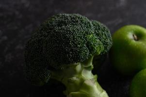 Brokkoli, Apfel und Avocado auf einem schwarzen Zementbodenhintergrund