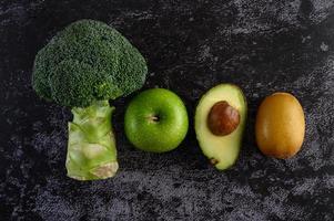 Brokkoli, Apfel, Kiwi und Avocado auf schwarzem Zementbodenhintergrund