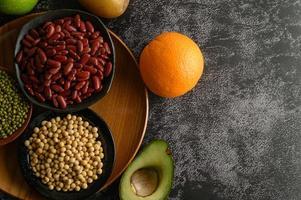 Hülsenfrüchte und Früchte auf schwarzem Zementbodenhintergrund