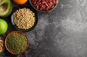 Hülsenfrüchte und Früchte auf schwarzem Zementbodenhintergrund foto