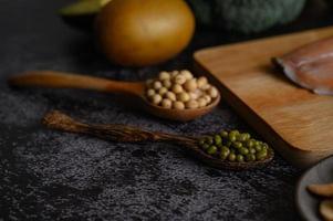 Hülsenfrüchte, Obst und Lachs auf einem schwarzen Zementhintergrund
