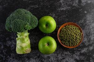 Brokkoli, Apfel und Mungobohne auf einem schwarzen Zementbodenhintergrund