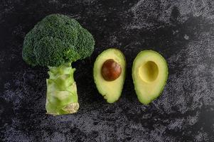 Brokkoli und Avocado auf schwarzem Zementbodenhintergrund