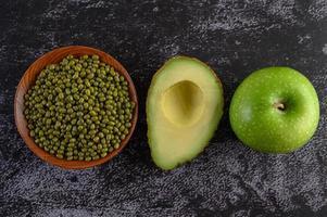 Mungobohne, Avocado und Apfel auf einem schwarzen Zementbodenhintergrund