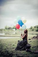 junge Frau, die bunte Luftballons in der Natur hält