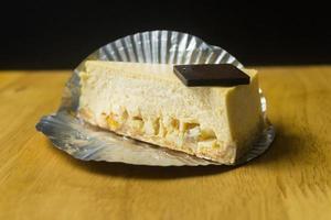 Nahaufnahme der Scheibe Käsekuchen auf Holztisch und dunklem Hintergrund foto