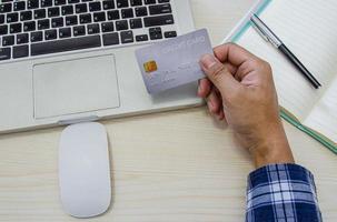 Hand hält eine graue Kreditkarte an einem Schreibtisch