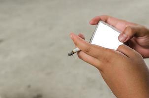 Person, die das Smartphone benutzt, während sie eine Zigarette raucht