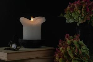 Kerze und Taschenuhr auf Buch foto