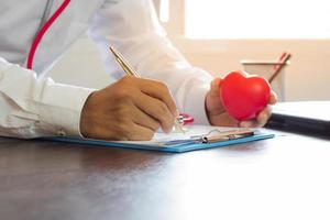 Arzt schreibt Rezept auf Papier und hält rotes Herz auf Arbeitstisch
