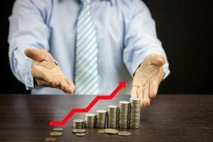 Geschäftsmann zeigt Geldwachstum foto