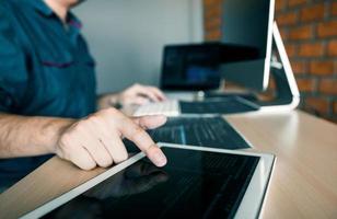 Softwareentwickler zeigt auf Tablet foto