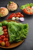 Limettenscheiben, Schalotten, Knoblauch, Tomaten, Salat und Paprika auf einem Holzteller