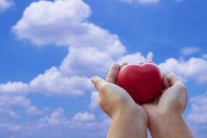 ein Spielzeug rotes Herz zum Himmel halten