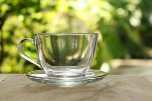 klares Glas auf dem Tisch draußen foto