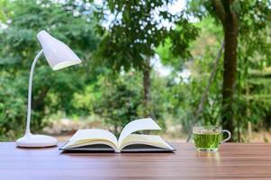 offenes Buch mit Tee und einer Lampe draußen foto