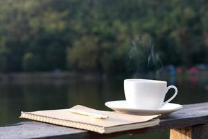 weiße Kaffeetasse mit Notizbuch