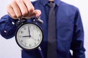 Mann hält eine Uhr