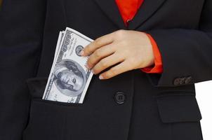 Mann steckt Geld in eine Anzugtasche foto