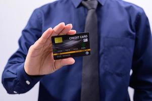 Mann hält eine schwarze Kreditkarte