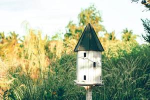 weißes Vogelhaus mit spitzem Dach foto