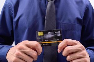 Mann hält schwarze Kreditkarte