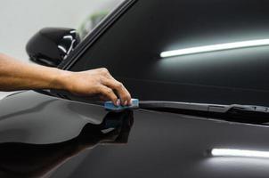 Reinigung der Motorhaube eines schwarzen Autos foto