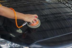 Hände polieren ein schwarzes Auto
