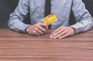 Person, die eine Kreditkarte an einem Schreibtisch hält