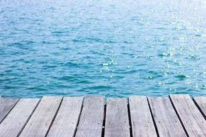 Holztischplatte für Anzeige mit blauem Wasser für Hintergrund foto