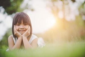 kleines Mädchen, das bequem auf Gras liegt und lächelt