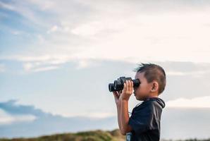 glückliches Kind, das mit Fernglas auf der Wiese spielt foto