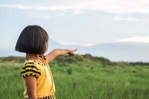 Mädchen zeigt mit der Hand zum Himmel