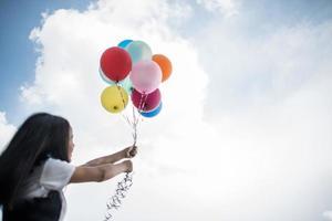 junges Mädchen, das bunte Luftballons in der Natur hält