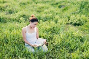 junge schöne asiatische Frau, die Buch auf der Wiese sitzt und liest