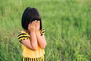 kleines Mädchen bedeckt ihr Gesicht