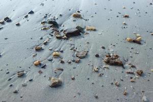 Kieselsteine auf grauem Sand foto