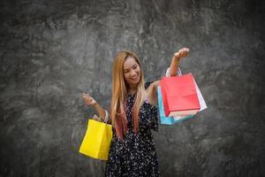 Porträt einer jungen glücklichen lächelnden Frau mit Einkaufstüten foto