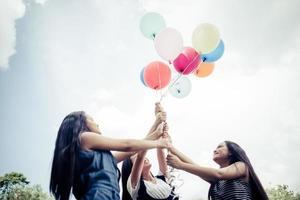 glückliche Gruppenfreundinnen, die bunte Luftballons an einem Park halten