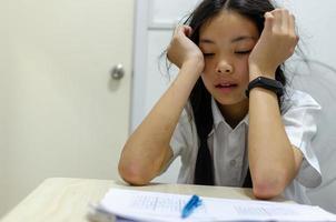 Schulmädchen kämpfen mit Hausaufgaben foto