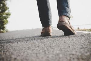 Nahaufnahme des jungen Touristenmannes, der auf einer Landstraße geht
