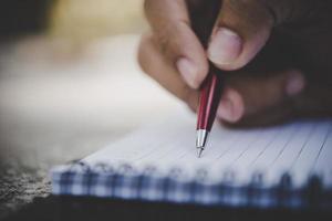 Mann Handschrift in seinem Notizbuch foto