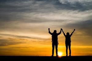 Silhouetten von zwei Wanderern mit Rucksäcken, die den Sonnenuntergang genießen foto