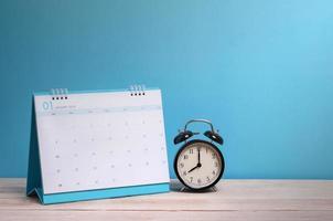 Uhr und Kalender auf Schreibtisch mit blauem Hintergrund foto