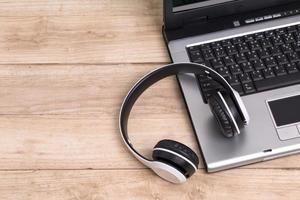 Kopfhörer und Laptop auf Holzschreibtisch foto