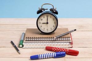 Uhr auf Notizbüchern mit Schreibgeräten