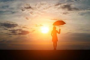 Silhouette einer Frau, die einen Regenschirm am Strand und am Sonnenuntergang hält foto