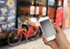 Hand, die das Smartphone auf unscharfem restaurentem Hintergrund hält foto