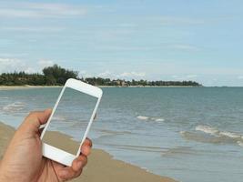 Person, die Telefon am Strand hält foto